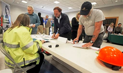 In this Thursday, April 3, 2013, photo, people fill out applications at the Green Mountain Flagging table at the 4th Annual Central Vermont Job Fair in Montpelier, Vt. (AP)