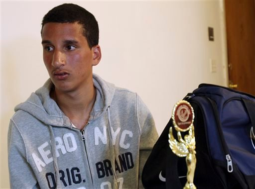 Salah Eddin Barhoum sits in his apartment in Revere, Mass., Thursday, April 18, 2013, with one of the trophies he won in an athletic competition, and the bag he was carrying on Monday near the finish line of the Boston Marathon.