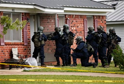 Armed federal agents wearing hazardous material suits and breathing apparatus entered the West Hills Subdivision home of Paul Kevin Curtis in Corinth, Miss., Thursday evening April 18, 2013. (AP Photo/Rogelio V. Solis)