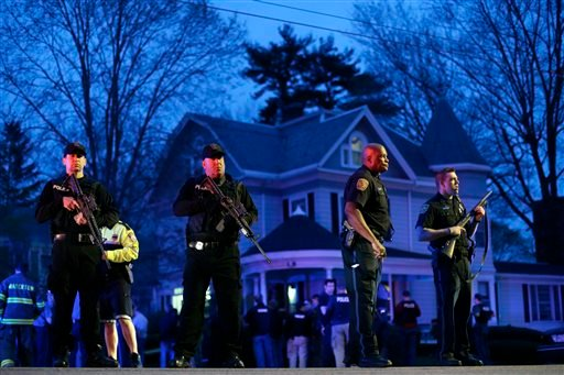 Police officers guard the entrance to Franklin street where there is an active crime scene search for the suspect in the Boston Marathon bombings, Friday, April 19, 2013, in Watertown, Mass. (AP Photo/Matt Rourke)