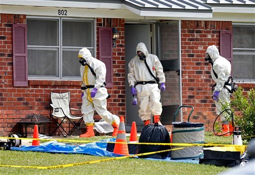 Federal agents wearing hazardous material suits and breathing apparatus exit the home and possessions in the West Hills Subdivision house of Paul Kevin Curtis in Corinth, Miss. April 19, 2013.(AP Photo/Rogelio V. Solis)