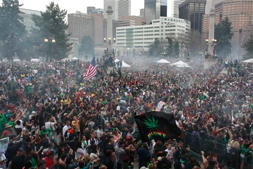 Members of a crowd numbering tens of thousands smoke marijuana simultaneously at 4:20 PM, at the Denver 420 pro-marijuana rally at Civic Center Park in Denver on Saturday, April 20, 2013. (AP Photo/Brennan Linsley)