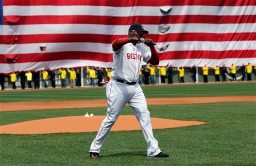 Boston Red Sox's David Ortiz pumps his fist in front of an Amarican flag and a line of Boston Marathon volunteers, background, after addressing the crowd before a baseball game between the Boston Red Sox and the Kansas City Royals.(AP Photo/Michael Dwyer