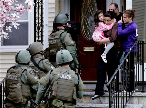 In this Friday, April 19, 2013 file photo, a woman carries a girl from their home as a SWAT team searching for a suspect in the Boston Marathon bombings enters the building in Watertown. (AP Photo/Charles Krupa, File)