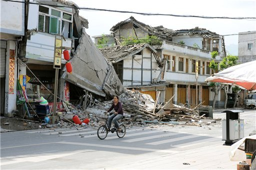 photo released by China's Xinhua News Agency, a local resident bicycles in front of collapsed houses after an earthquake struck in Lushan County, Ya'an City, in southwest China's Sichuan Province, Saturday, April 20, 2013. (AP Photo/Xinhua, Jin Xiaoming)