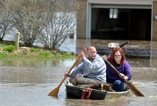 Chad Keedy and stepdaughter Jordan DeBolt, 15, of Chillicothe, Ill., paddle through flood waters in their neighborhood along Oak Lawn Street in Chiilicothe, Ill., on Saturday, April 20, 2013. (AP Photo/Peoria Journal Star, Ron Johnson)