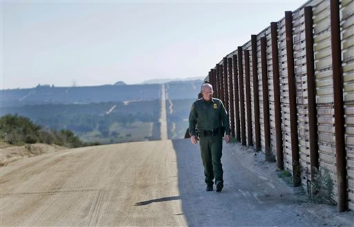 In this Monday, March 25, 2013 photo, Border Patrol agent Richard Gordon, a 23-year veteran of the agency, walks the border fence in the Boulevard area east of San Diego.
