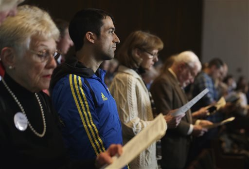 Wearing his Boston Marathon runner's jacket, David Delmar, 28, second from left, a member of Trinity Episcopal Church in Boston, attends a service at Temple Israel, which allowed the Trinity congregation to hold their service, Sunday, April 21, 2013.