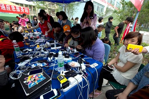People charge their mobile phones at a relief center in the county seat of Lushan in southwestern China's Sichuan province, Monday, April 22, 2013.