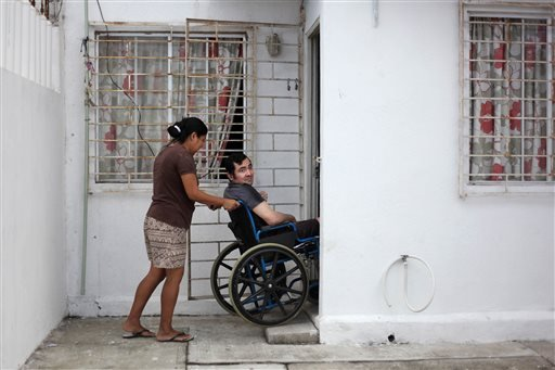 In this Thursday March 7, 2013 photo, Jacinto Rodriguez Cruz, 49, leaves his home on a wheelchair with the help of his wife, Belen Hernandez in the city of Veracruz, Mexico.