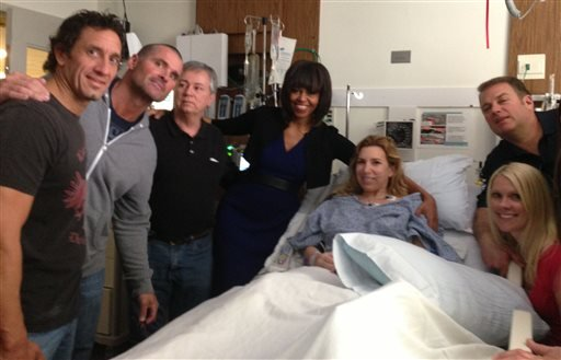 This April 18, 2013 photo provided by Alfred Colonese shows from left Alfred Colonese, Mick Henn, Dale Abbott, first lady Michelle Obama, Heather Abbott, Jason Geremia, and Michelle Dalrymple at Brigham and Women's Hospital in Boston.