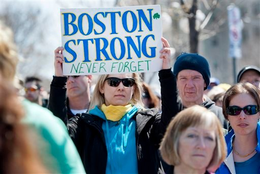 Ottawa runner Shelley Baran holds a sign in tribute to the victims of the Boston Marathon bombings, at the United States Embassy in Ottawa after marching in solidarity with the Boston community on Monday, April 22, 2013.
