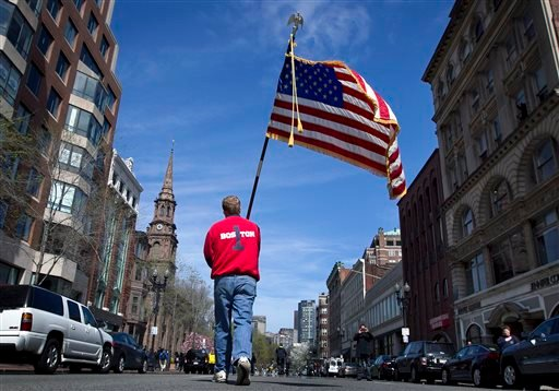 Lt. Mike Murphy of the Newton, Mass., fire dept., carries an American flag down the middle of Boylston Street after observing a moment of silence in honor of the victims of the bombing at the Boston Marathon near the race finish line.