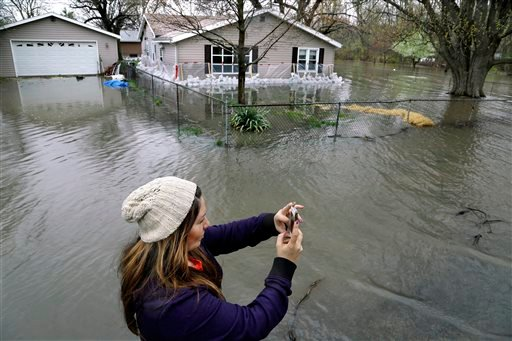 Jennifer Rock uses her cell phone to take photos to send to a friend of flooding from the Illinois River Tuesday, April 23, 2013, in Spring Bay Ill. Floodwaters are rising to record levels along the Illinois River in central Illinois. (AP Photo)