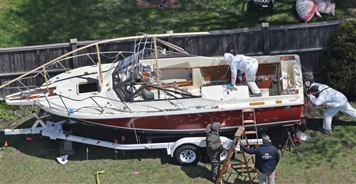 Investigators from the FBI inspect the boat where Boston Marathon bombing suspect Dzhokhar Tsarnaev was found hiding on Friday night in a backyard in Watertown, Mass., Tuesday, April 23, 2013. (AP)