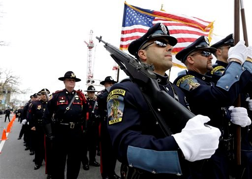 Members of a police honor guard, front, lead a column of law enforcement officials into a memorial service for fallen MIT police officer Sean Collier, in Cambridge, Mass., April 24, 2013.