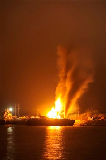 Fire burns aboard two fuel barges Wednesday April 24, 2013 along Mobile River after explosions sent three workers to the hospital. (AP Photo John David Mercer)