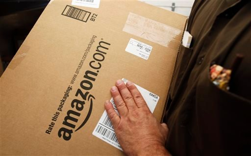 In this Oct. 18, 2010 file photo, an Amazon.com package is prepared for shipment by a United Parcel Service (UPS) driver in Palo Alto, Calif.