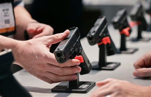 In this Wednesday, Jan. 16, 2013 file photo, a Glock representative explains features of the Glock 37 Gen 4 .45 caliber pistol at the 35th annual SHOT Show, in Las Vegas.