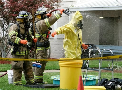 Firefighters decontaminate their comrade who investigated a suspicious letter which caused the closure of the Kirkman building on Monday, April 29, 2013, in Tallahassee, Fla.