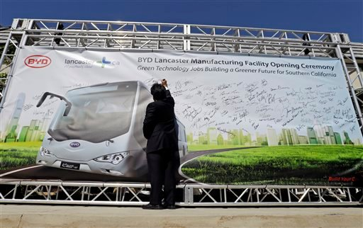 A visitor writes on a banner during a news conference announcing the opening of an electric bus manufacturing plant by Chinese-owned vehicle manufacturer BYD Automotive in Lancaster, Calif. on Wednesday, May 1, 2013. (AP)