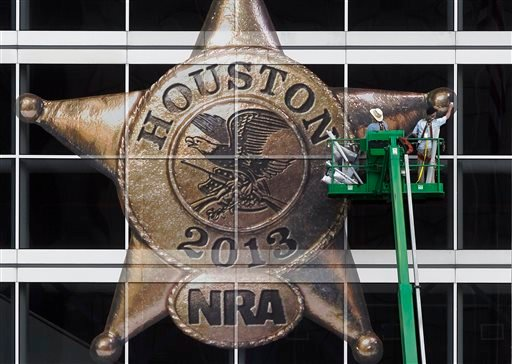 The National Rifle Association logo is placed on the George R. Brown Convention Center by Lynn Creel, left, and Don Reynolds of Display Graphics on Wednesday, May 1, 2013, in Houston.