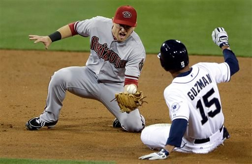 Arizona Diamondbacks shortstop Cliff Pennington, left, bobbles and drops the throw at second base as San Diego Padres' Jesus Guzman, right, safely steals the base in the fourth inning during their baseball game Friday, May 3, 2013, in San Diego.