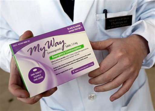 This Thursday, May 2, 2013 photo shows pharmacist Simon Gorelikov holding a generic emergency contraceptive at the Health First Pharmacy in Boston.