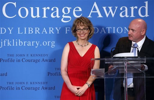 Former Arizona congresswoman Gabrielle Giffords, left, stands with her husband Capt. Mark Kelly after receiving the John F. Kennedy Profile in Courage Award in Boston, Sunday, May 5, 2013. (AP Photo/Michael Dwyer)