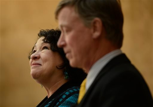 In this Thursday, May 2, 2013 file photo, Supreme Court Justice Sonia Sotomayor, next to Colorado Governor John Hickenlooper, looks up at the crowd during a dedication of the new Ralph L. Carr Colorado Judicial Center in Denver.