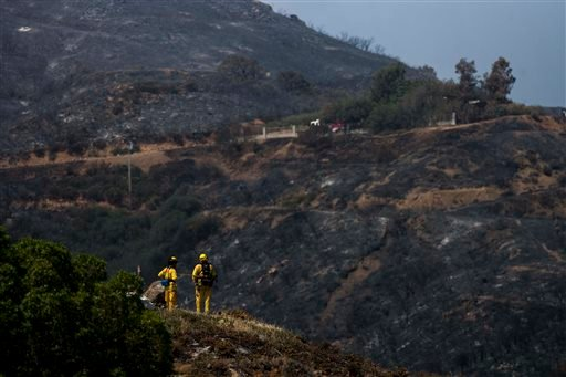 Crews work on the fire line after a wildfire near Point Mugu, Calif., Saturday, May 4, 2013. High winds and withering hot, dry air was replaced by the normal flow of damp air off the Pacific, significantly reducing fire activity.