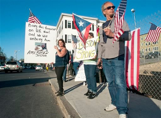 From left, Lisa Taurasi, Lucy Rodriguez and Luis Barbosa, all of Worcester, Mass., hold protest signs as they stand across the street from Graham Putnam & Mahoney Funeral Parlors in Worcester, Mass. on Sunday evening, May 5, 2013. (AP)