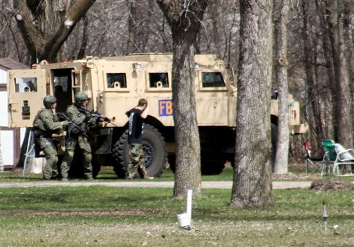 This May 3, 2013, photo provided by Jeremy Jones shows authorities with Buford Rogers, right, during a raid on a mobile home in Montevideo, Minn. (AP)
