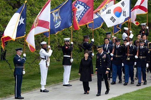 Visiting South Korea President Park Geun-hye, center left, is escorted by Maj. Gen. Michael Linnington, as they march past the colors of American states, during a wreath laying ceremony at the Tomb of the Unknowns at Arlington National Cemetery.