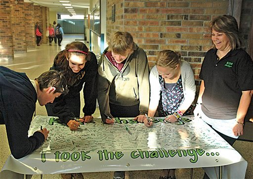 This Nov. 3, 2011 photo shows, from left, Brock Raffaele of Cadillac, Mich. and Sault High students Lauren Gee, Conner Langendorf, and Emma Harrington, taking the KDR Challenge and sign the banner in Sault Ste. Marie, Mich.