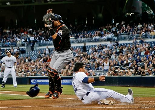 San Diego Padres' Everth Cabrera slides past Miami Marlins catcher Miguel Olivo while scoring from third on a sacrifice fly by Yonder Alonso during the first inning of a baseball game in San Diego, Tuesday, May 7, 2013. (AP photo/Lenny Ignelzi)