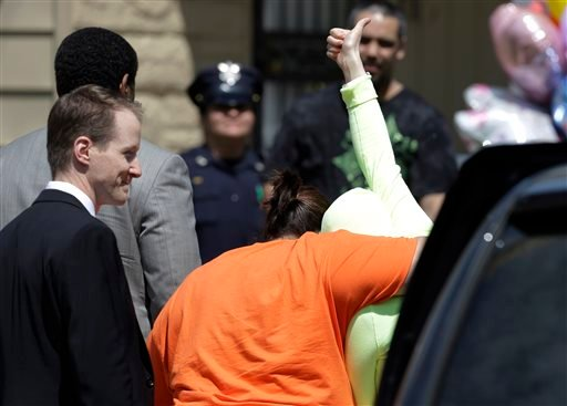 Gina DeJesus gives a thumbs-up as she is escorted toward her home Wednesday, May 8, 2013, in Cleveland. (AP)