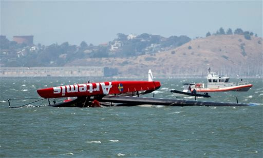 The overturned Artemis Racing AC72 catamaran, an America's Cup entry from Sweden, is towed past Treasure Island after the boat capsized during training in San Francisco Bay on Thursday, May 9, 2013, in San Francisco, Calif. (AP)