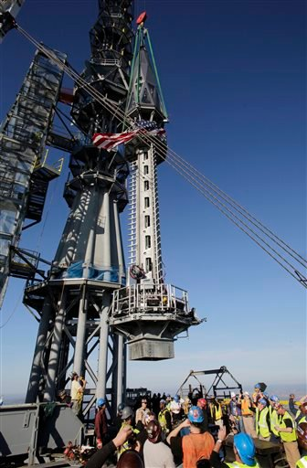 The final piece of spire is hoisted in place on top of One World Trade Center, Friday, May 10, 2013 in New York.