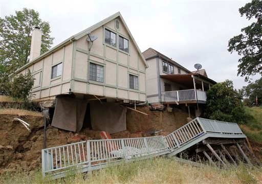 In this photo taken Monday, May 6, 2013, the bedroom carpets hang from the home of Jagtar Singh, left, after the ground gave way in Lakeport, Calif.