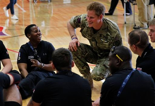 Britain's Prince Harry talks with members of the British Warrior Games Team who relaxed in a gymnasium before the opening of 2013 Warrior Games, at the U.S. Olympic Training Center, in Colorado Springs, Colo., Saturday May 11, 2013.