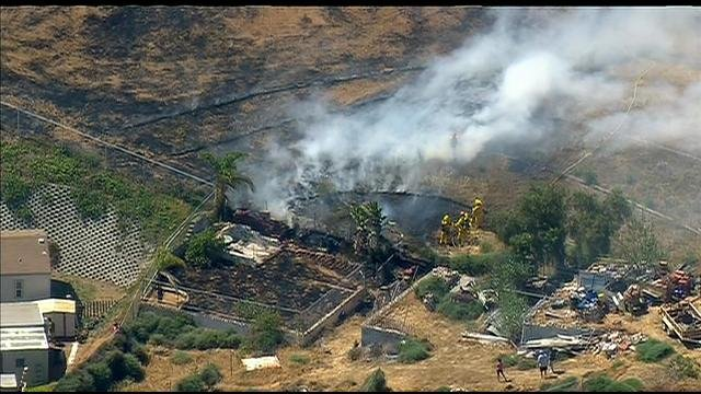 Images from Chopper 8 show plumes of smoke as a small brush fire burns near homes.