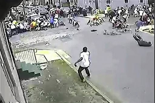 In this image taken from video and provided Monday, May 13, 2013, by the New Orleans Police Department, a possible shooting suspect in a white shirt, bottom center, shoots into a crowd of people, Sunday in New Orleans.