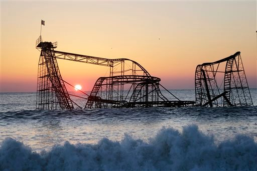 In a Feb. 25, 2013 file photo, the sun rises in Seaside Heights, N.J., behind the Jet Star Roller Coaster which has been sitting in the ocean after part of the Casino Pier was destroyed during Superstorm Sandy.