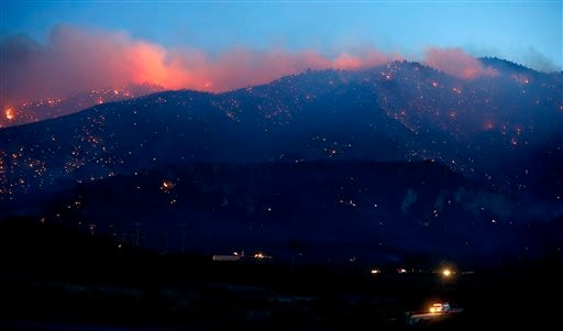 Cooler temperatures and lighter winds are helping hundreds of firefighters combat a 3,000-acre wildfire. (AP Photo/Los Angeles Times, Luis Sinco)