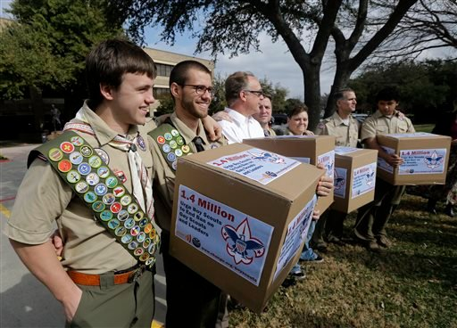 In this Feb. 4, 2013 file photo, James Oliver, left, hugs his brother and fellow Eagle Scout, Will Oliver, who is gay, as Will and other supporters carry four boxes filled with petitions to end the ban on gay scouts and leaders in front of the Boy Scouts