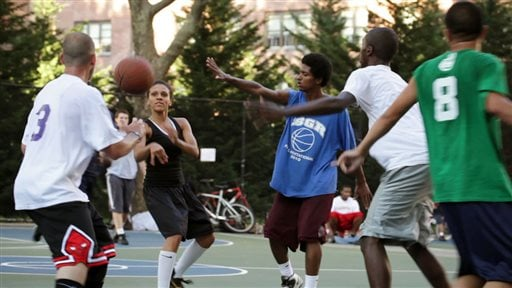 "This film publicity image released by Doin' It In The Park, LLC shows female basketball player Niki Avery, second left, playing basketball in the Spanish Harlem section of New York during filming of the documentary ""Doin' It In The Park."""