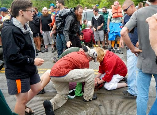 People attend to a victim who was hit by a car during the Hikers Parade at the Trail Days festival in Damascus, Va., Saturday, May 18, 2013. (AP Photo/Republican-American, Bill O'Brien)