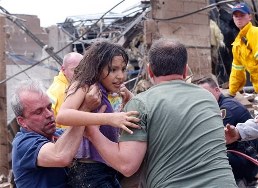 A child is pulled from the rubble of the Plaza Towers Elementary School in Moore, Okla., and passed along to rescuers Monday, May 20, 2013. A tornado as much as a mile wide with winds up to 200 mph roared through the Oklahoma City suburbs Monday.