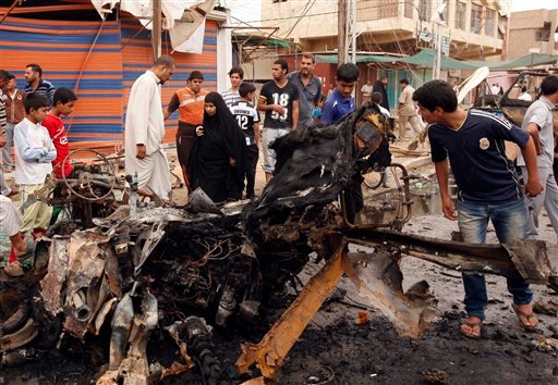 Civilians inspect the scene of a car bomb attack in the Kamaliyah neighborhood, a predominantly Shiite area of eastern Baghdad, Iraq, Monday, May 20, 2013. (AP Photo/ Hadi Mizban)